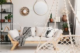 verschwommene hängesessel in den vordergrund und hölzernen sofa im wohnzimmer interieur mit spiegel echtes foto stockfoto und mehr bilder beige