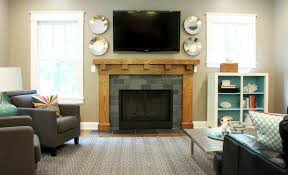 gray brick fireplace with light brown wooden frame plus tv above