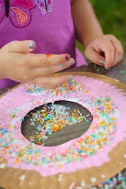 Child Sprinkling Coloured Rice Onto A Paper Plate Donut Craft