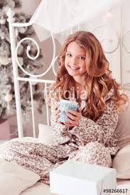 happy teen 8 10 year old sitting in bed with cup of tea in