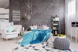 einem schönen schlafzimmer mit bequemen bett und stilvoll weißen sessel