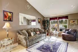 wohnzimmer innenraum mit hohen gewölbten decke und beige teppichboden mit oliven sofa braun liebe sitz und glastischen eingerichtet