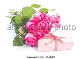 Bouquet of pink roses next to a t with a blank card Stock