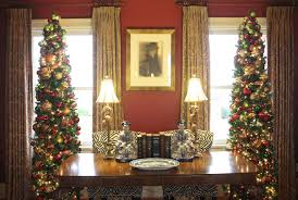 Slim Line Trees Decorated In Burgundy Gold And Shades Of Green Illuminate Each The Homes Four Front Windows Arlene Rogers Doesnt Use Tree Toppers