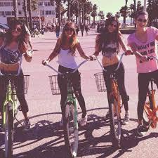 Four Friends Riding Bikes And Having Fun At Venice Beach California