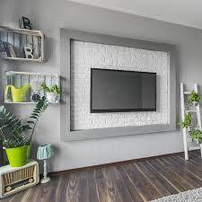 großer fernseher und kreative dekorationen im hellen wohnzimmer mit holzboden