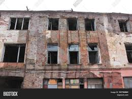 Abandoned Destroyed Damaged Rundown Old Apartment House Building Facade With Broken Glass Windows Renovation