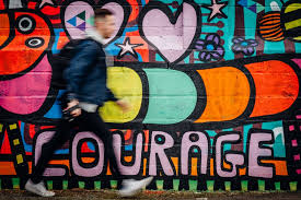 Fashionable Young Man With Backpack And Denim Jacket Walking Past Colorful Courage Typography Graffiti