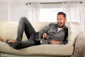 hübsche und attraktive 30er oder 40er jahre weißer mann beim fernsehsportprogramm oder zu hause liegen entspannt und kühl auf dem