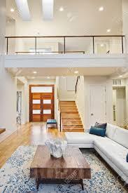 schöne und ein großes wohnzimmer interieur mit holzböden und gewölbten decken in neuen luxus haus mit offenem grundriss mit blick auf eingang und