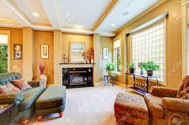 schönes wohnzimmer mit großem fenster kamin und getrimmt decke viele dekor