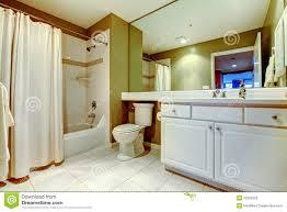 grünes und weißes badezimmer mit wanne und wanne mit vorhang