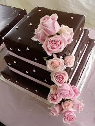 Chocolate is used for filling this white cake Decorated with pink ribbon & fresh cascade pink roses
