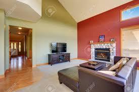 gewölbte decke wohnzimmer mit schwarzer ledercouchgarnitur kamin und roten kontrast wand northwest usa