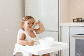 baby 1 4 jahre alt sitzen auf hohen kinder stuhl und essen gemüse allein in der weißen küche