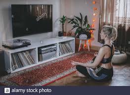 junge frau meditiert im wohnzimmer gesund zu hause bleiben