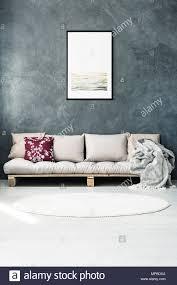 hell poster auf dunklen wand über beige sofa mit kissen in