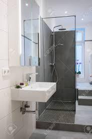 moderne gehobene badezimmer interieur mit einer wand in neutralen tönen rechteckigen handwaschbecken duschkabine aus glas und fliesenböden und wände