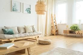zwei poster pflanzen hängen über ein bequemes sofa mit kissen in einem hellen hölzernen wohnzimmer interieur