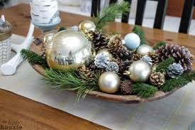 A Wooden Bowl With Pinecones Ornaments And Greenery
