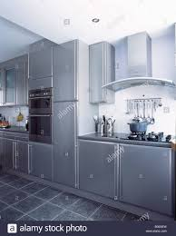 wall mounted ovens in modern metallic grey kitchen with slate