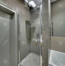 moderne badezimmer mit langen fliesen an den wänden und boden es gibt eine duschkabine mit glastür weißes bad tür chrom handtuchhalter leuchtende