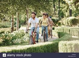 Cute Sporty Friends Riding Bikes In Park Group Of Friendly Students Spending Time Together Outside Summer Vacation Concept