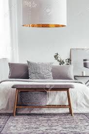 weiße designerle über holzbank auf kopiertem teppich im schlafzimmer mit grauen kissen auf bett