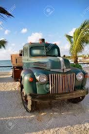 An Old Antique Full Ton Pickup Truck Is Parked Near Some Palm ...