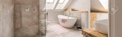 beige teppich auf dem boden vor weißer badewanne im grauen badezimmer im dachboden mit duschsatz