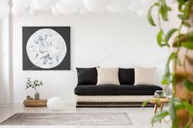 kissen auf schwarzem sofa in weißen wohnzimmer interieur mit mond po foto bialasiewicz auf envato elements