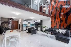stylisches offenes wohnzimmer mit gestalteten stühlen ledersofa und roten und schwarzen wandfliesen