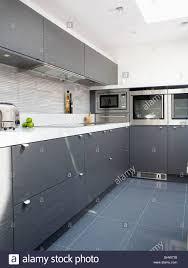 grey ceramic floor tiles in modern white kitchen with gray