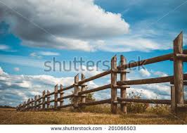 Wooden Rustic Fence In Village And Blue Sky With Clouds