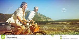 Download Smiling Couple Riding Their Bikes On The Beach Stock Illustration