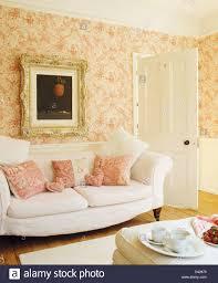 kunstvoll gerahmten bild über dem weißen sofa mit rosa