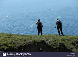 Two People Stand On A Cliff Edge Looking Out The Celtic Sea Great Saltee Island In Wexford Ireland