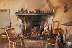 Interior Of An Old Country House Where A Dog Gets Hot Inside The Fireplace Stock Photo