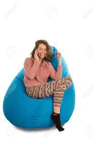 lachende junge frau die auf blauem sitzsack für wohnzimmer oder anderen raum sitzt und am telefon lokalisiert auf weißem hintergrund spricht