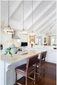 three white half pendant lights hang from a vaulted
