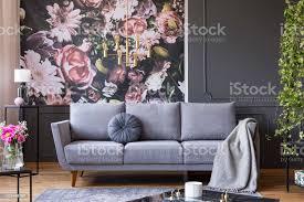 industrielle golden pendelleuchte und schwarzen möbeln in einem dunklen wohnzimmer interieur mit blumentapete und eine graue stockfoto und mehr
