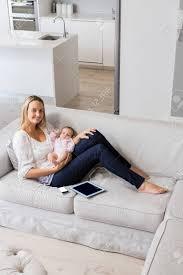 portrait der lächelnden mutter sitzt mit ihrem baby im wohnzimmer zu hause