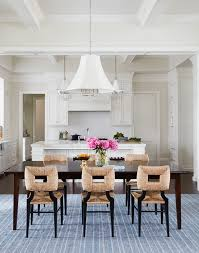 A White Pleated Chandelier Illuminates Mahogany Stained Rectangular Dining Table Lined With Seagrass Chairs Placed Atop Denim Blue Striped Rug