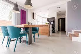 monochromatische moderne offene wohnung mit bunten und hölzernen akzenten im esszimmer und küche mit treppe und türeingang