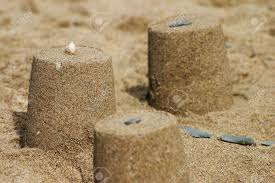 Simple Sandcastle Constructed From Wet Sand Sparsely Decorated With A Shell And Small Pebbles