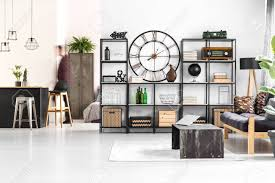 runde uhr und radio auf dem regal im sommer wohnzimmer mit laptop auf tisch und hocker an der kücheninsel