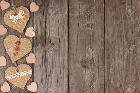Side Border Of Handmade Burlap Hearts With Ribbon And Buttons Over A Rustic Wooden Background Stock