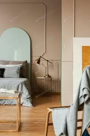 goldene le auf modernen nachttisch neben blauem bett in grauem schlafzimmer interieur foto bialasiewicz auf envato elements