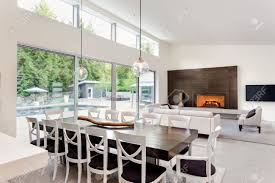 schöne wohnzimmer und esszimmer mit kamin und blick auf terrasse mit pool und große glasschiebetüren