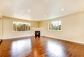 leeres wohnzimmer mit poliermassivholzboden und eckenkamin